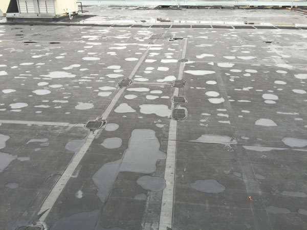 Defective Adhesives - Patches on a EPDM rubber roof indicates a premature failure of a roofing system.